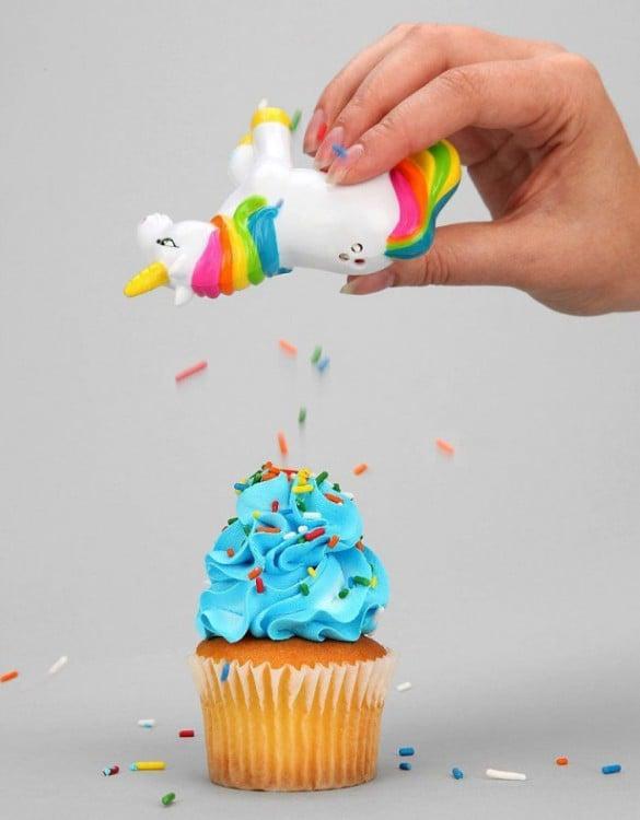 dispensador de especias en forma de unicornio poniendo chispas a un cupcake