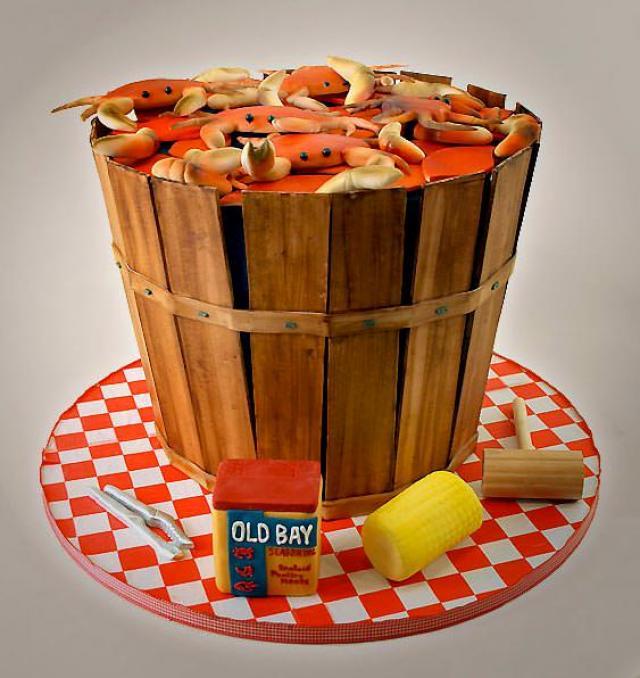 diseño de un pastel en forma de una cubeta con cangrejos y algunos casos alrededor