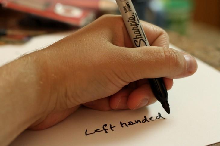 mano izquierda de una persona escribiendo con un plumón sobre un papel