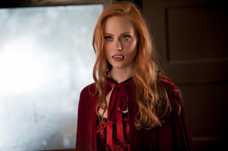 Mujer pelirroja con dientes y capa de vampiro