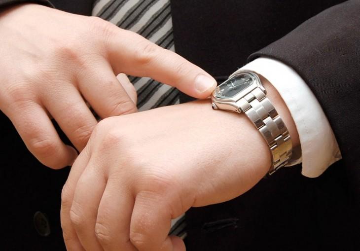 manos de una persona señalando un reloj con una mano