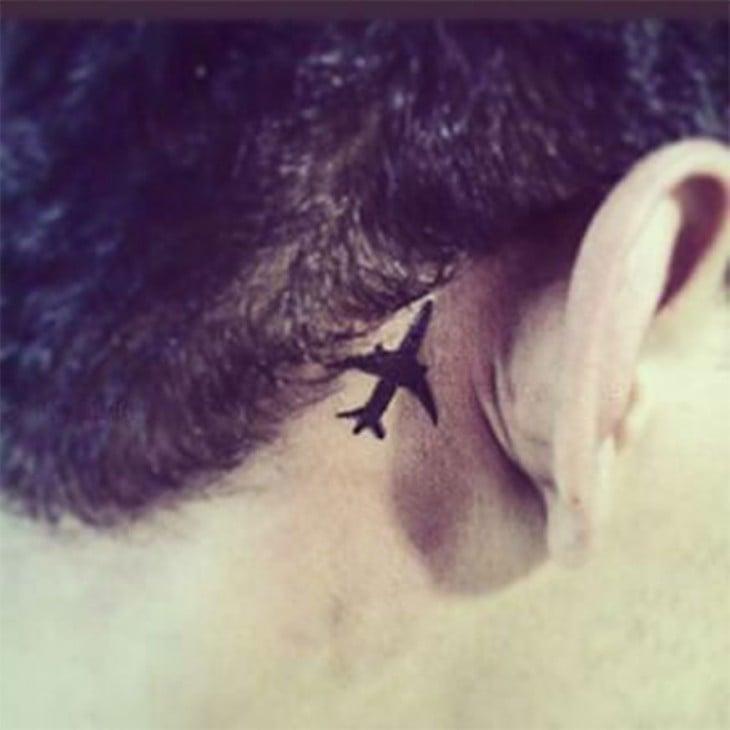 tatuaje de avión detrás de la oreja