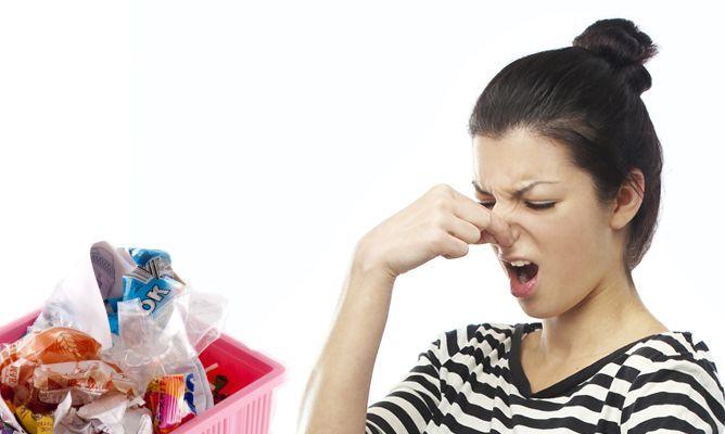 mujer tapando su nariz frente a un bote de basura