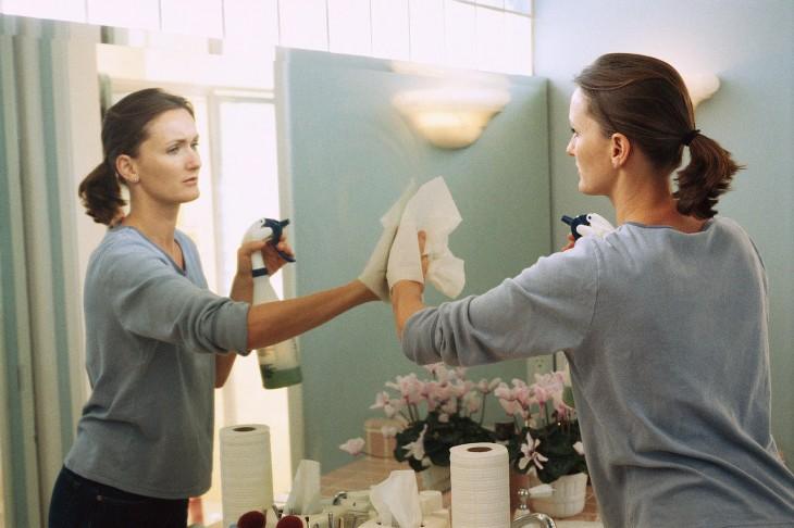 mujer limpiando un espejo con una toalla de papel