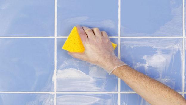 mano limpiando azulejos con un estropajo lleno de sal y vinagre