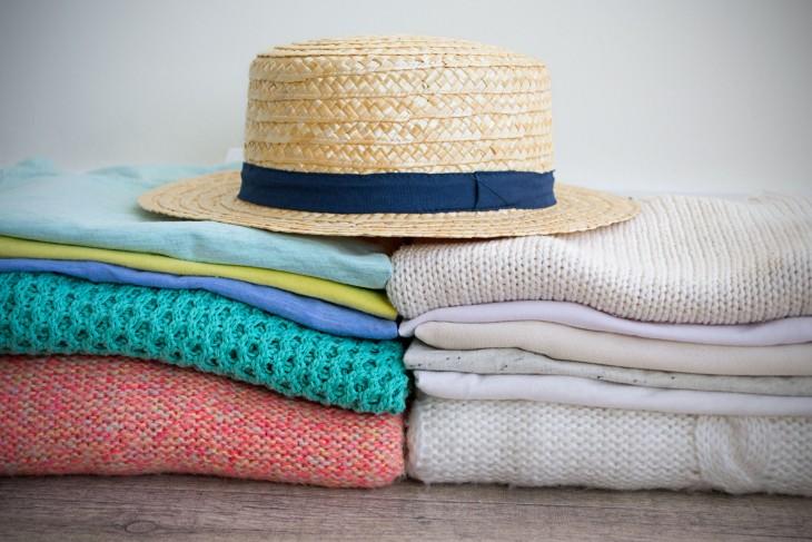 ropa recién planchada y doblada con un sombrero encima