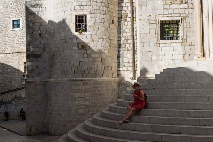 una chica sentada en unas escaleras en Dubrovnik