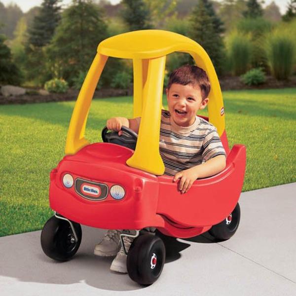 niño pequeño sobre un pequeño carro Little Tikes