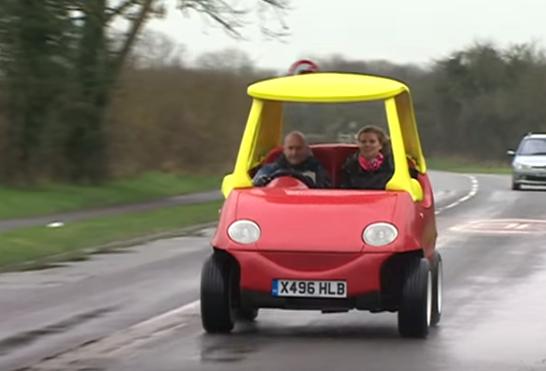 personas sobre el coche de juguete en tamaño real