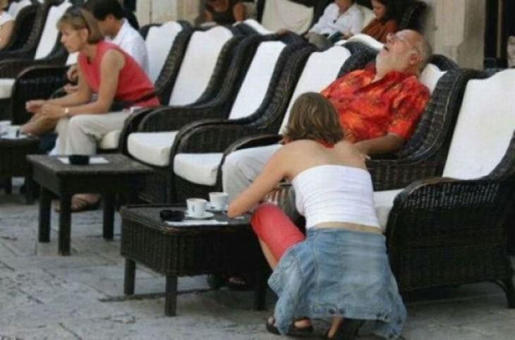 hombre sentado en un sillón dormido y a un lado una chica agachada