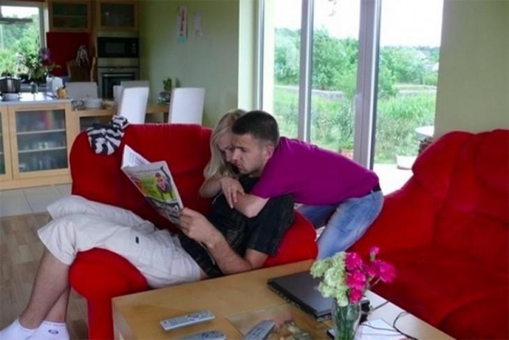 una chica abrazando a un chico que esta sentado en un sillón leyendo un periódico