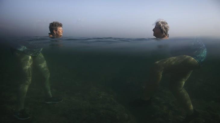 dos mujeres dentro del agua donde solo se ven sus cabezas