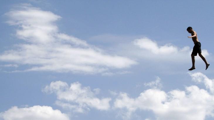 chico dando un salto a un río que simula estar volando por el cielo