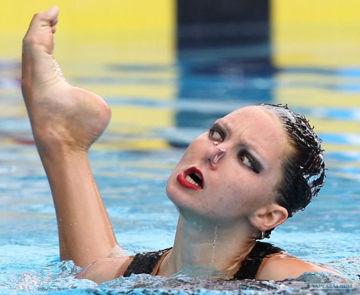 chica dentro de una piscina con un pie a un costado de su cabeza