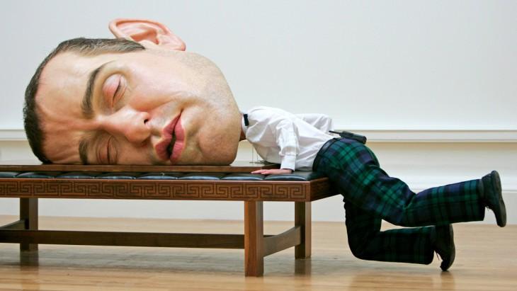 hombre recargado sobre un escritorio con una escultura de una cabeza gigante