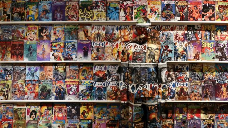 chico camuflajeado entre muchas revistas puestas en un estante