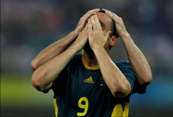 medio cuerpo de un futbolista que parece tener cuatro brazos agarrando su cabeza