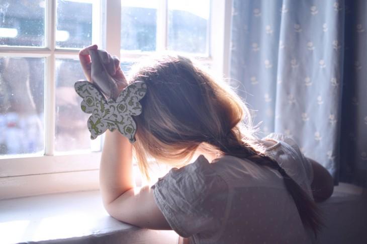 niño conpungida sobre la ventana