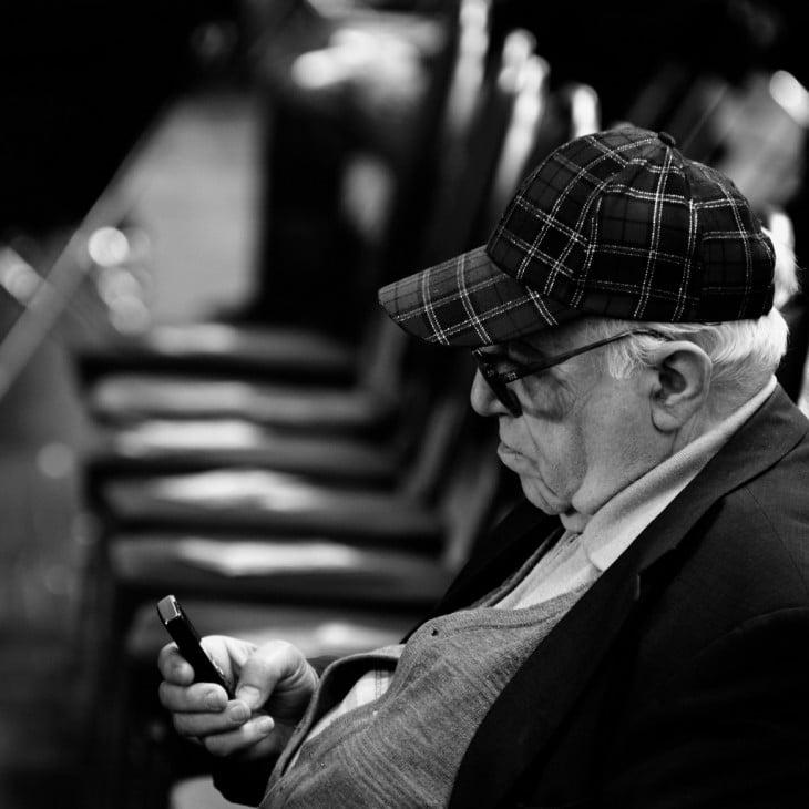 hombre viendo su celular en la calle