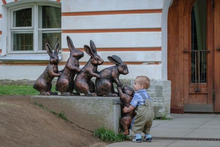 Este pequeño intenta ayudar a una estatua a subir porque se ha quedado atras