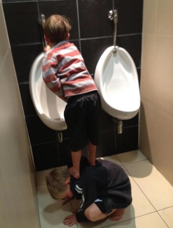 niño ayudandole a orinar a su primo en un mingitorio
