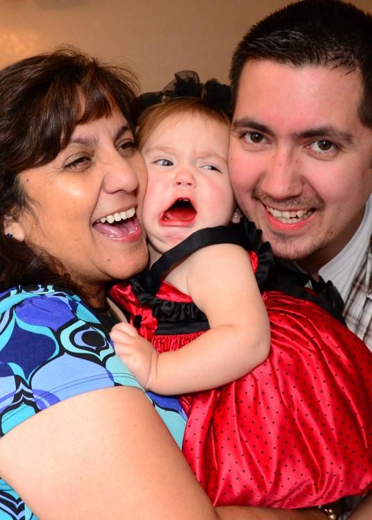 niña llorando mientras su abuela y su padre le aplastan la cara