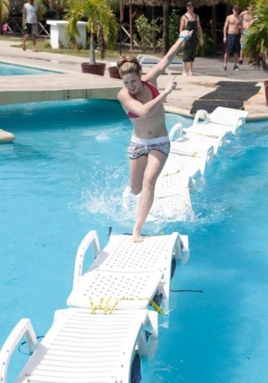 mujer pasando el cerco de sillas en la alberca brincando sin resbalarse