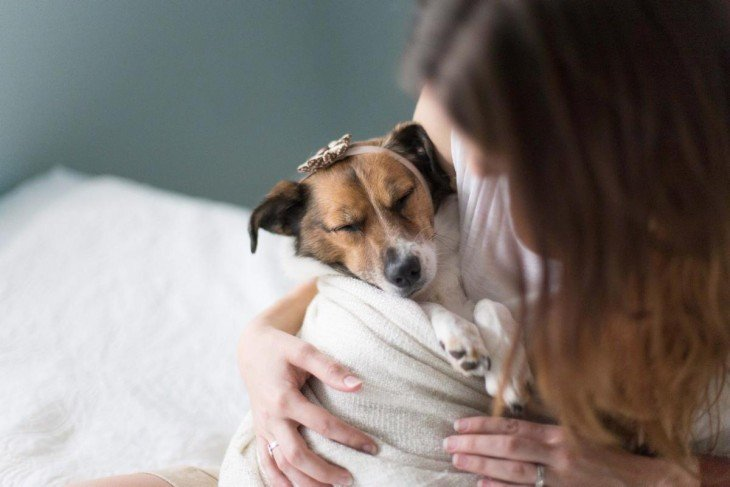 pareja se retrata con su perro como si fuera un bebé