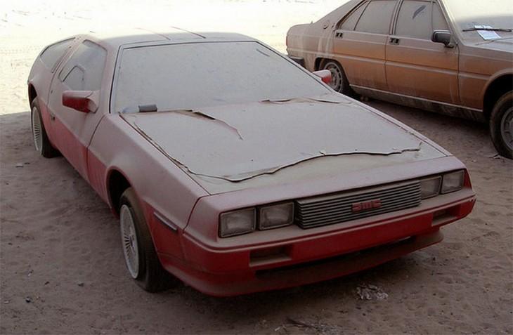Carro DeLorean rojo abandonado en un estacionamiento en Dubái