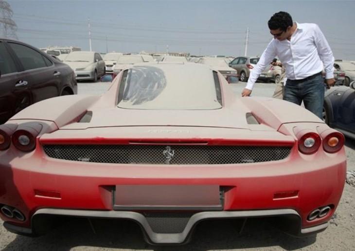 hombre dibujando sobre el polvo de un ferrari rojo abandonado en un estacionamiento de Dubai