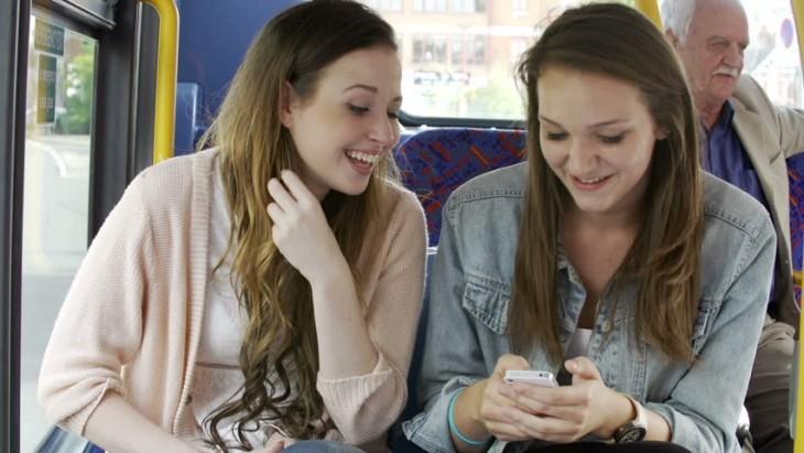 Dos chicas distraídas en el autobús