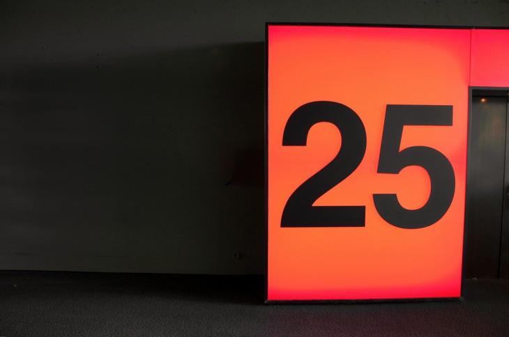 número 25 sobre un fondo en color naranja y negro
