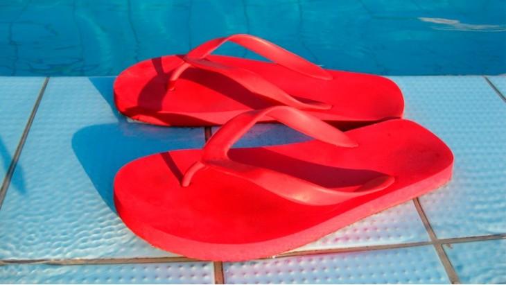 sandálias em vermelho na beira de uma piscina