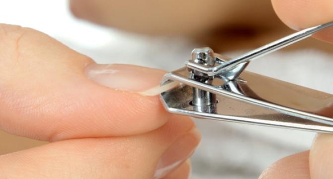 persona cortándose la uña de un dedo