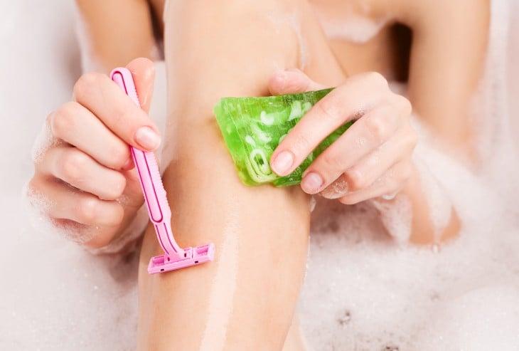 piernas de mujer depilándose con un rastrillo en color rosa