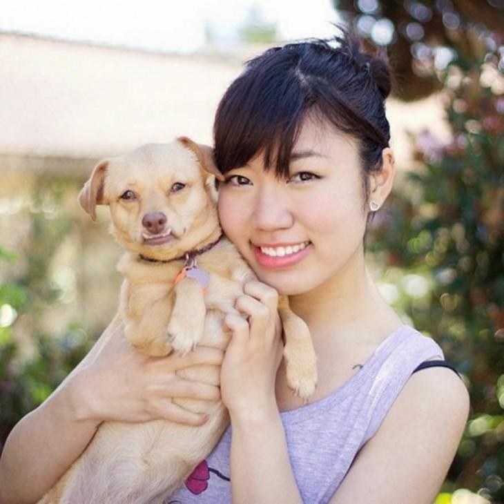 chica cargando a un perro en sus brazos