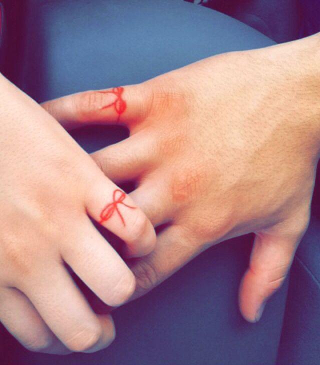 dos manos con un tatuaje en el meñique de un moño hecho en color rojo
