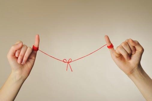foto de dos manos con los dedos meñiques atados con un hilo rojo