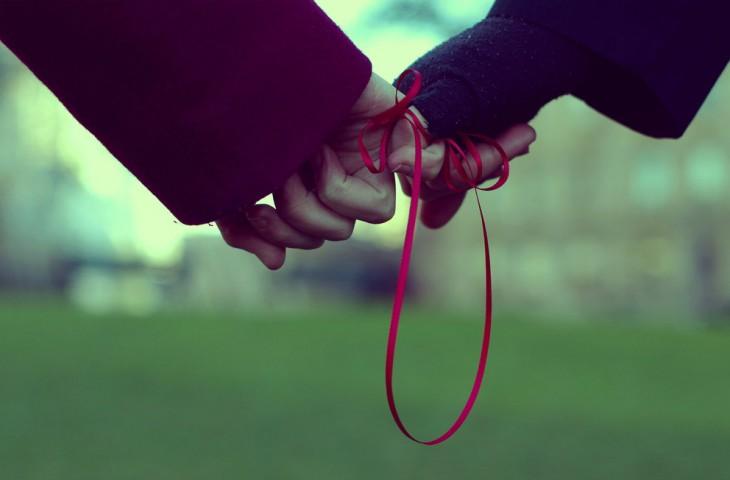 dedos de personas entrelazados atados con un listón en color rojo