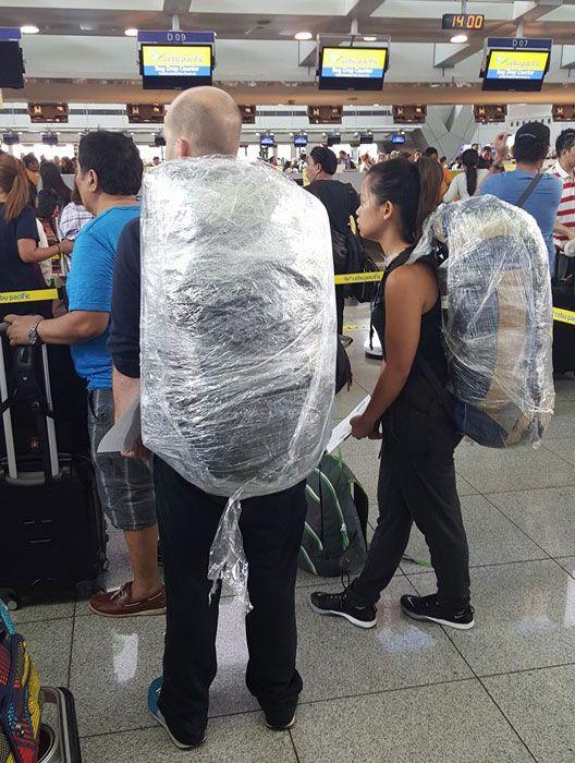 Pasajeros dentro de un aeropuerto con sus equipajes cellados con papel transparente