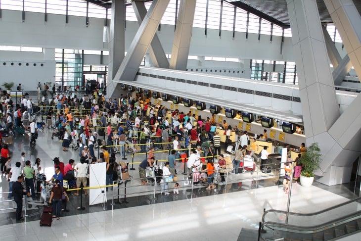 filas de personas con sus equipajes dentro de un aeropuerto