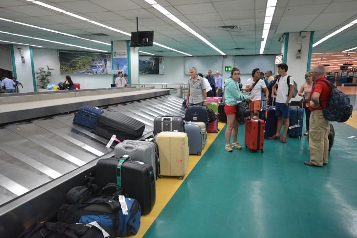 personas recogiendo su equipaje después de pasar por los rayos x
