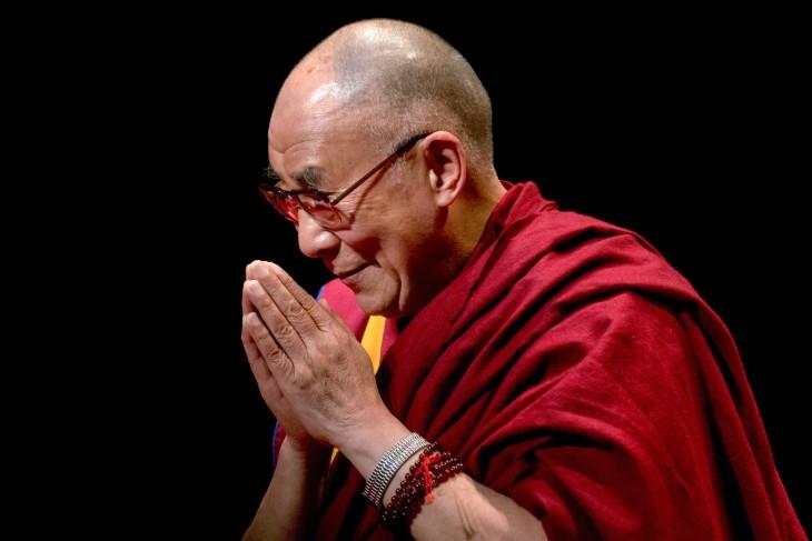 Dalai Lama con la cabeza un poco inclinada con sus manos juntas haciendo oración