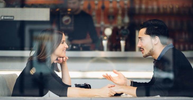 um homem e uma mulher sentada em uma mesa em um restaurante de mãos dadas falando