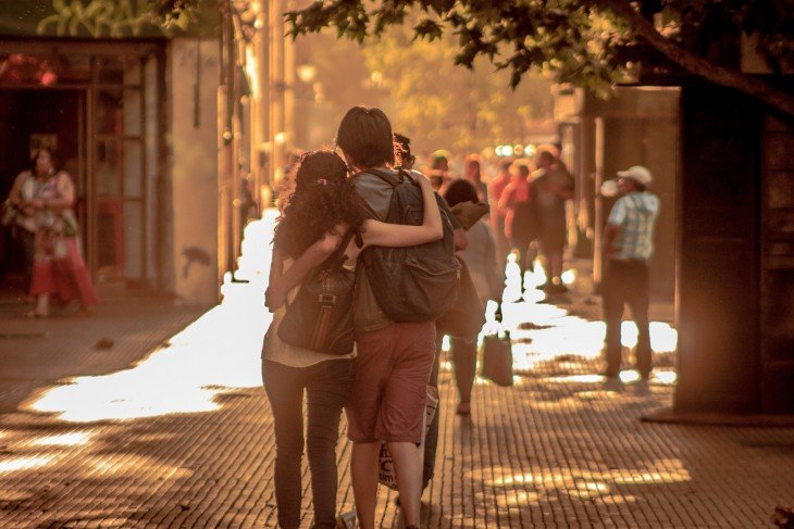 Una pareja de novios abrazados caminando por una calle