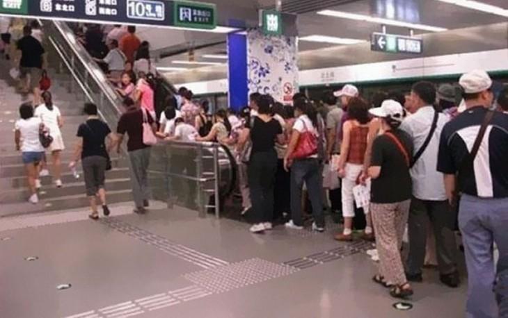 Personas haciendo fila para subir por las escaleras eléctricas