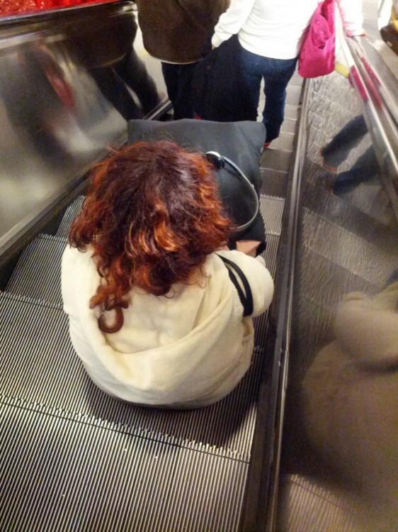 una mujer sentada en un escalón de las escaleras eléctricas