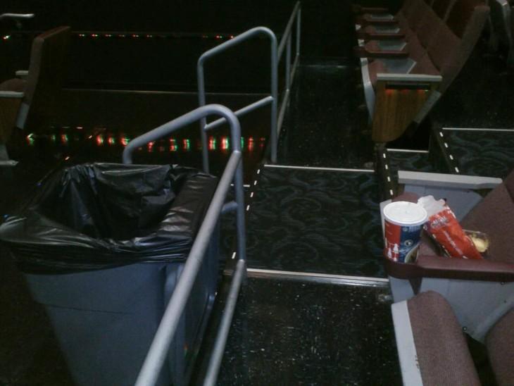 sala de un cine con basura en un asiento estando un bote de basura enfrente