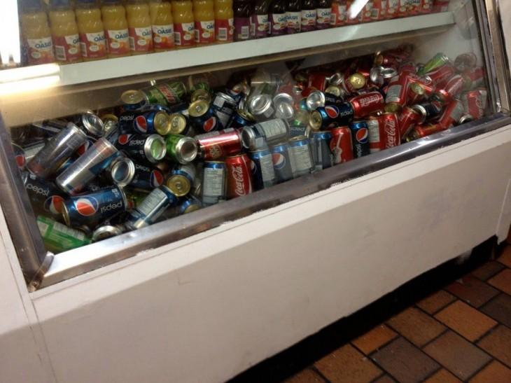 un refrigerador lleno de refrescos desordenados