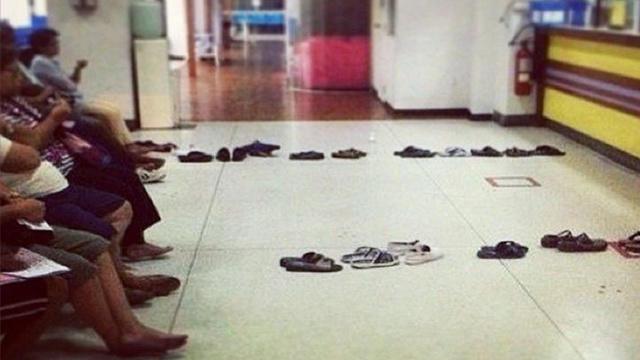 personas sentadas con sus zapatos haciendo fila